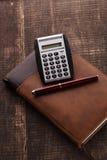 El cuaderno, la calculadora y la pluma imagenes de archivo