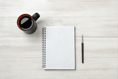El cuaderno, la taza de coffe y el lápiz pusieron la tabla Fotos de archivo