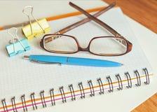 El cuaderno, los vidrios, la pluma, y los clips para el documento sobre la tabla emergen Foto de archivo