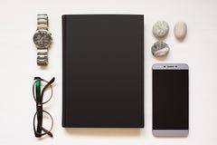 El cuaderno negro en blanco aislado en blanco texturizó el fondo de madera con cosas del ` s del hombre de negocios Libro plano d Foto de archivo