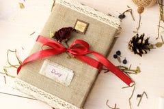 El cuaderno para escribir sueños y las memorias adornados con la cinta roja brillante y lindos secan color de rosa Concepto román Imagenes de archivo