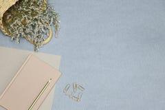 El cuaderno rosado, clips de papel, cesta de la paja con las flores en el escritorio azul imagen de archivo libre de regalías
