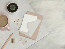 El cuaderno, el sobre de plata, lápiz, sacapuntas, clips de papel, pernos, taza del café, cactus, en la tabla del granito y el bl imagen de archivo