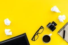 El cuaderno, tinta, pluma de la inmersión, café, vidrios para el lugar de trabajo del escritor fijó en maqueta amarilla de la opi Fotos de archivo