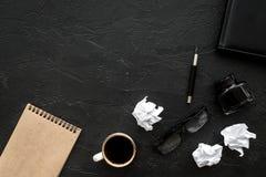 El cuaderno, tinta, pluma de la inmersión, café, vidrios para el lugar de trabajo del escritor fijó en maqueta oscura de la opini Fotos de archivo