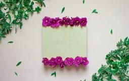 El cuaderno vac?o adorn? las flores p?rpuras en un fondo blanco, visi?n superior Libreta adornada con las hojas y la violeta verd stock de ilustración