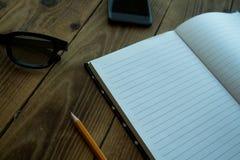 El cuaderno y el lápiz y el reloj llaman por teléfono a los vidrios en bacground de madera imagen de archivo