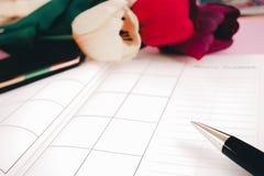 El cuaderno y la pluma en blanco del planeamiento con las flores en el escritorio nos utilizan vida del horario del organizador o Fotografía de archivo