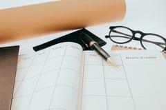 El cuaderno y la pluma en blanco del planeamiento en el escritorio nos utilizan vida del horario del organizador o concepto del p Fotografía de archivo