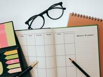 El cuaderno y la pluma en blanco del planeamiento en el escritorio nos utilizan vida del horario del organizador o concepto del p Foto de archivo