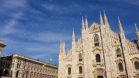 El cuadrado de la catedral de Milán con un cielo azul y los globos amarillos se van volando almacen de video