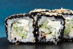 El cuadrado japonés rueda con las huevas negras del tobiko, semillas de sésamo, crema Imágenes de archivo libres de regalías