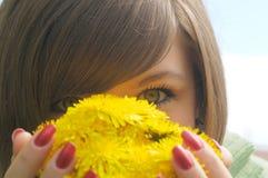 El cuadro del primer de la mujer eyes detrás de la flor amarilla imagen de archivo