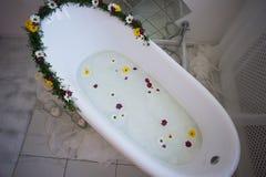 El cuarto de baño lujoso se adorna con las flores y las velas Con un espejo grande Fotografía de archivo