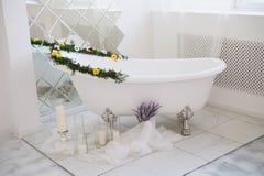 El cuarto de baño lujoso se adorna con las flores y las velas Con un espejo grande Fotografía de archivo libre de regalías