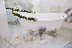 El cuarto de baño lujoso se adorna con las flores y las velas Con un espejo grande Imágenes de archivo libres de regalías