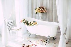 El cuarto de ba?o est? en un cuarto ligero adornado con las flores y los p?talos de rosas foto de archivo