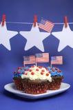 Banderas americanas de los E.E.U.U. con las estrellas que cuelgan de clavijas en una línea y de magdalenas con el espacio de la co Fotografía de archivo