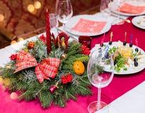 El cubierto de la tabla de la Navidad con el pino de la Navidad ramifica, cinta y arco Días de fiesta de Navidad y del Año Nuevo Imagen de archivo libre de regalías