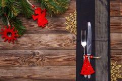 El cubierto de la tabla de la Navidad con la bifurcación y cuchillo, juguete adornado de la Navidad, los copos de nieve del oro y Fotografía de archivo