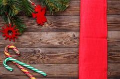 El cubierto de la tabla de la Navidad, pino adornado de la Navidad ramifica con los juguetes de la Navidad, el bastón de dos piru Fotografía de archivo libre de regalías