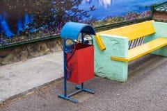 El cubo de la basura metálico, hermoso se coloca cerca de un banco, en la acera Foto de archivo libre de regalías