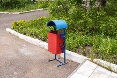 El cubo de la basura metálico se coloca cerca de un banco, en la acera Fotografía de archivo