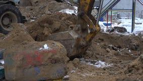 El cubo del excavador cava la tierra metrajes