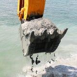 El cubo del excavador de agua coge el suelo del fondo del mar Foto de archivo libre de regalías