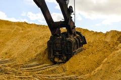 El cubo enorme del excavador cava la arena en la explotación minera de la mina de la arena imagen de archivo