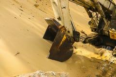 El cubo enorme del excavador cava la arena en la explotación minera de la mina de la arena imagenes de archivo