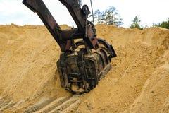 El cubo enorme del excavador cava la arena en la explotación minera de la mina de la arena fotos de archivo