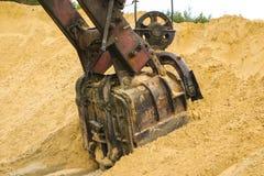 El cubo enorme del excavador cava la arena en la explotación minera de la mina de la arena foto de archivo