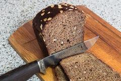 El cuchillo cortó un pedazo de pan imagen de archivo