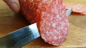 El cuchillo corta al gastrónomo del ingrediente de la salchicha del salami almacen de metraje de vídeo