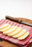 El cuchillo de cocina en un tablero de madera y una patata cubre en el paño Fotografía de archivo libre de regalías