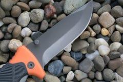 El cuchillo de la supervivencia en los guijarros oscila piedras fotografía de archivo libre de regalías
