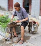El cuchillo de pulido del viejo hombre en la ciudad antigua zhenyuan, Guizhou, China fotografía de archivo libre de regalías
