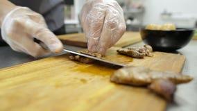 El cuchillo del cocinero corta las aves almacen de metraje de vídeo