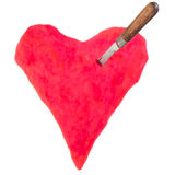 El cuchillo entonado de la imagen con la manija de madera se pegó en corazón rojo grande Imagen de archivo libre de regalías