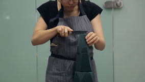 El cuchillo grande del florista corta la forma de cono de una esponja floral verde metrajes