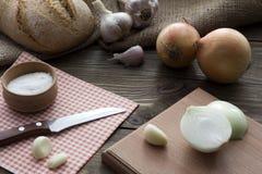 El cuchillo, la cebolla, el ajo, el pan y la sal Imagen de archivo