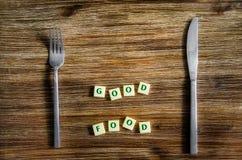 El cuchillo y la bifurcación fijaron en la tabla de madera, buena muestra de la comida Imagen de archivo libre de regalías