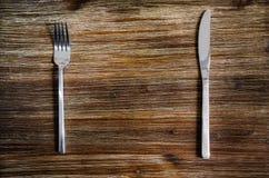 El cuchillo y la bifurcación fijaron en una tabla de madera Imagen de archivo libre de regalías