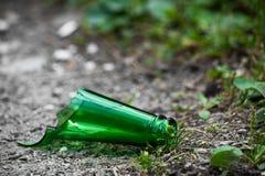 El cuello de una botella de cristal verde quebrada miente en la calle imágenes de archivo libres de regalías
