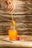 El cuenco con la miel en la tabla de madera El banco de la estancia de la miel cerca de la cuchara de madera Imagen de archivo libre de regalías