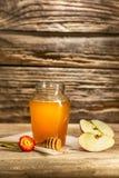 El cuenco con la miel en la tabla de madera El banco de la estancia de la miel cerca de la cuchara de madera Imágenes de archivo libres de regalías