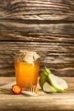 El cuenco con la miel en la tabla de madera El banco de la estancia de la miel cerca de la cuchara de madera Foto de archivo libre de regalías