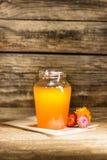El cuenco con la miel en la tabla de madera El banco de la estancia de la miel cerca de la cuchara de madera Imagenes de archivo