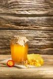 El cuenco con la miel en la tabla de madera El banco de la estancia de la miel cerca de la cuchara de madera Fotografía de archivo libre de regalías